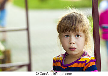 Little girl with funny expression on her face playing outdoors