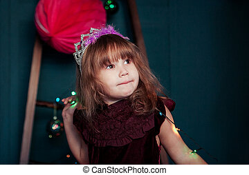 little girl with garlands on christmas background