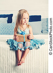 Little Girl with Gift Box. Cute Child at Home (2 years old)