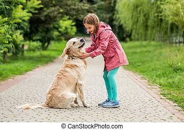 Little girl with golden retriever in park