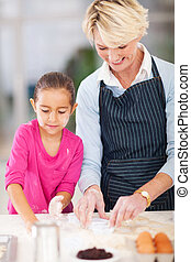 little girl with grandmother baking in kitchen