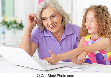 little girl   with granny using laptop