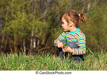 little girl with grass in hands sits on fringe of forest