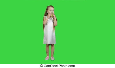 Little girl with green apple, eating it on a Green Screen, Chroma Key