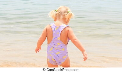 little girl with hairtails backside walks in shallow seawater