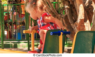 little girl with hairtails climbs up and down of swing
