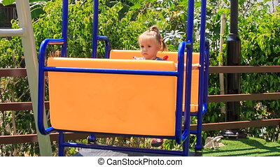 little girl with hairtails in checked swings on playground