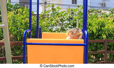 little girl with hairtails in white swings on playground