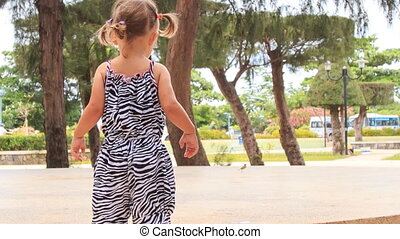 little girl with hairtails in zebra dress walks roundabout park