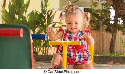 little girl with hairtails rocks on swing on playground in park