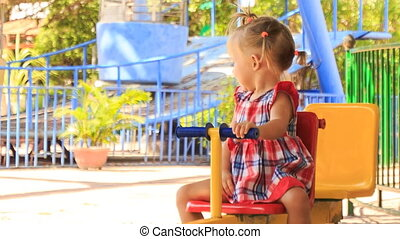 little girl with hairtails rocks on swing waves hand in park