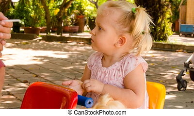 little girl with hairtails sits on swing drinks with straw