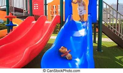 little girl with hairtails slides down on playground