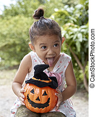 Little girl with halloween pumpkin