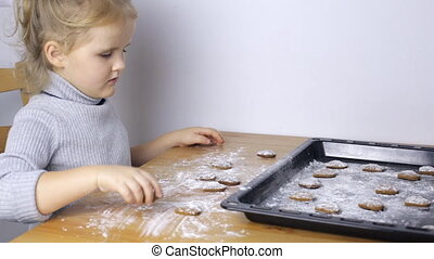 Little girl with handmade heart shaped cookies in kitchen