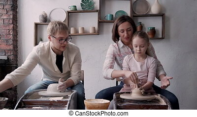 Little girl with happy family making craft pottery in small work.