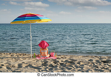 little girl with hat sitting under sunshade on beach