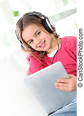 Little girl with headphones and electronic tablet