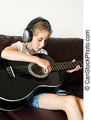 Little girl with headphones playing the guitar.
