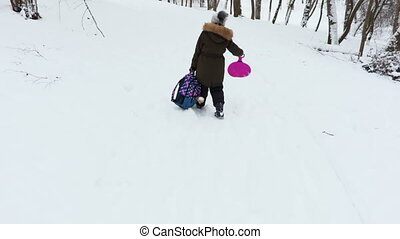 Little girl with heavy backpack on snow covered path