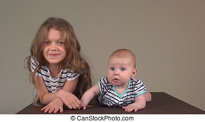 Little girl with her baby sister. The children hold hands. elder sister and younger sister together. Slow motion