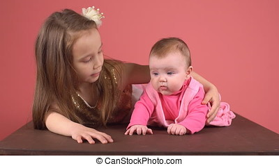 Little girl with her baby sister. The children hold hands.