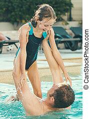 Little girl with her dad having fun in swimming pool.