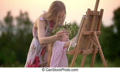 Little girl with her mom paints on easel outdoors at summer sunset