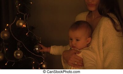 little girl with her mother at christmas tree