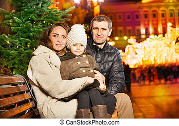 Little girl with her parents at the city square