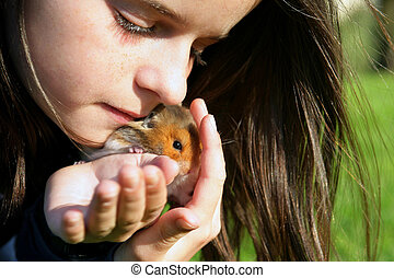 Little girl with her pet hamster