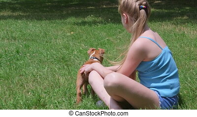 Little girl with her puppy dog on a grass