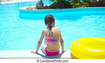 Little girl with inflatable rubber circle in swimming pool