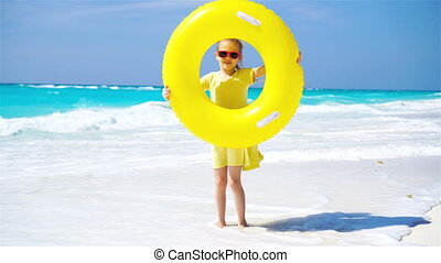 Little girl with inflatable rubber circle on beach vacation