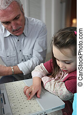 little girl with laptop and granddad watching upon her