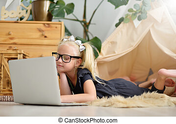 Little girl with laptop on the floor in her room