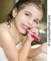 Little girl with lipstick on the bathroom