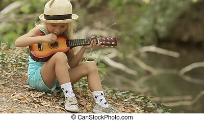 Little girl with long blond hair in straw hat playing guitar