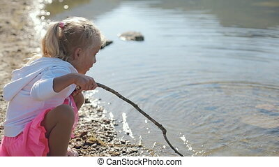 Little girl with long blond hair leads stick on the lake water