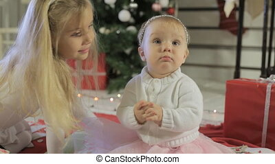 Little girl with long blond hair with her kid sister near Christmas tree