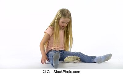Little girl with long blonde hair is holding hedgehog at white background. Girl in pink T-shirt and jeans. Curious hedgehog is sniffing at studio. Slow motion