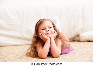 little girl with long hair lies on a floor