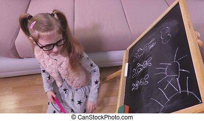 Little girl with magic wand near blackboard