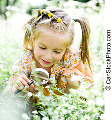 Little girl with magnifying glass looks at flower - pretty...