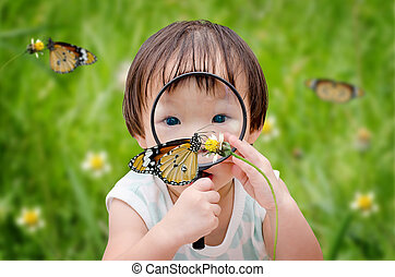 little girl with magnifying glass outdoors