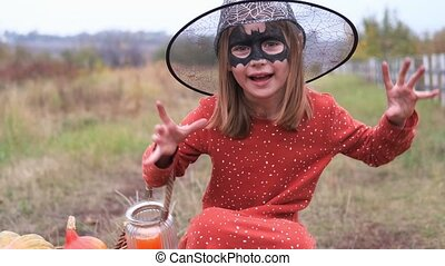 Little girl in hat and halloween face makeup frightening at camera and smiling on nature background