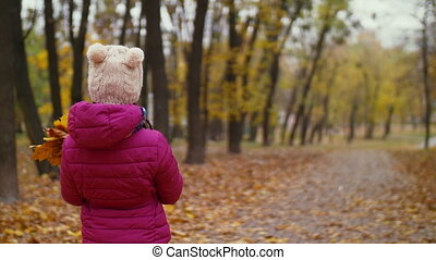 Little girl with maple leaves walking in autumn park - Rear...