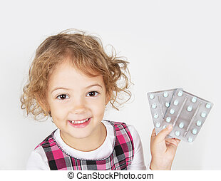 little girl with medicines in hand