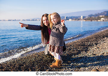 Little girl with mom having fun on the beach in a winter day