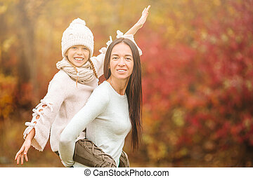 Young mother with cute little girl in autumn park on sunny day. Family enjoy warm weather at september day